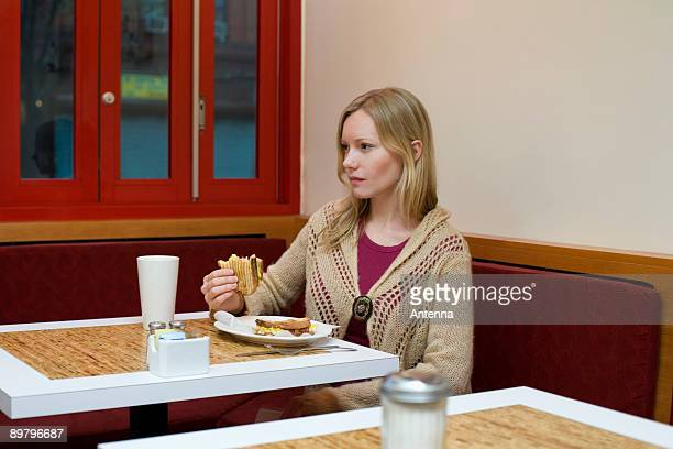 A young woman sitting in a cafe and eating a toasted sandwich