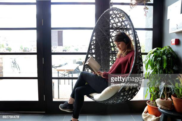 young woman sitting in a cafe wearing headphones and reading a book - maroon stock pictures, royalty-free photos & images