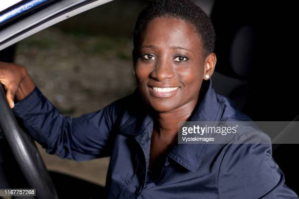 young woman sitting in a car, hands on the steering wheel smiling at the camera. - femme ivoirienne photos et images de collection