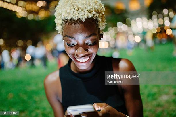 Young woman sitting in a park at night looking at cell phone