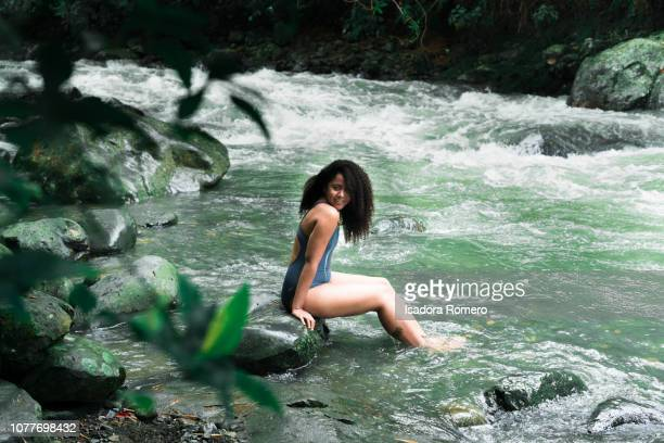 young woman sitting in a rock in the river - cali colombia stock pictures, royalty-free photos & images