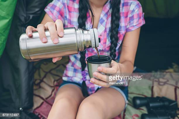 Young woman sitting in a tent pouring coffee from thermos flask into cup, partial view