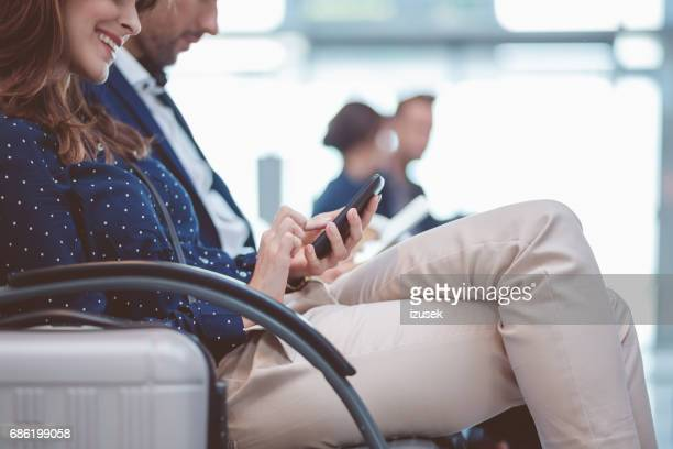 Young woman sitting in airport lounge using mobile phone