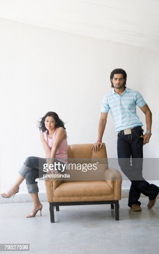 Young Woman Sitting In An Armchair With A Young Man ...