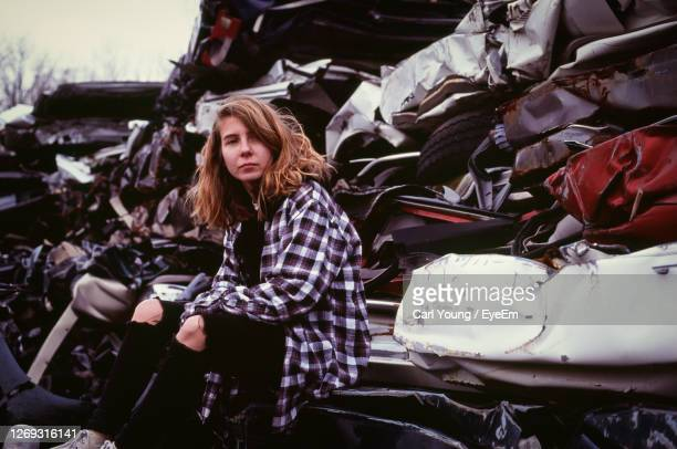 young woman sitting in an auto salvage yard - homelessness stock pictures, royalty-free photos & images