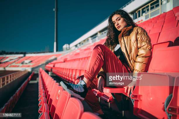 young woman sitting in an empty sports stadium outdoors - audience free event stock pictures, royalty-free photos & images