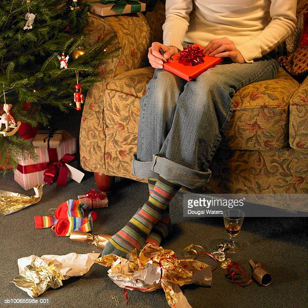 Young woman sitting in armchair unwrapping christmas present, low section