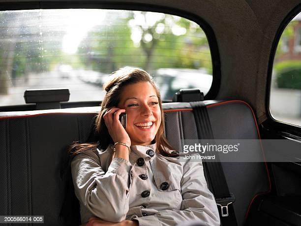 Young woman sitting in back of taxi, talking on mobile phone, smiling