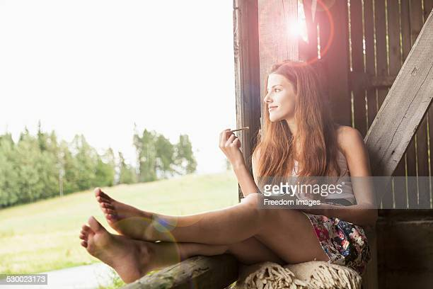 Young woman sitting in barn with notebook