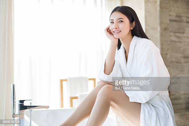Young woman sitting in bathroom