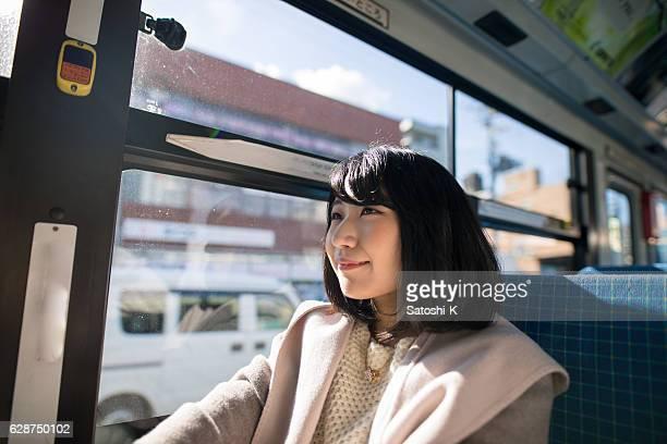バスに座っている若い女性 - 乗る ストックフォトと画像