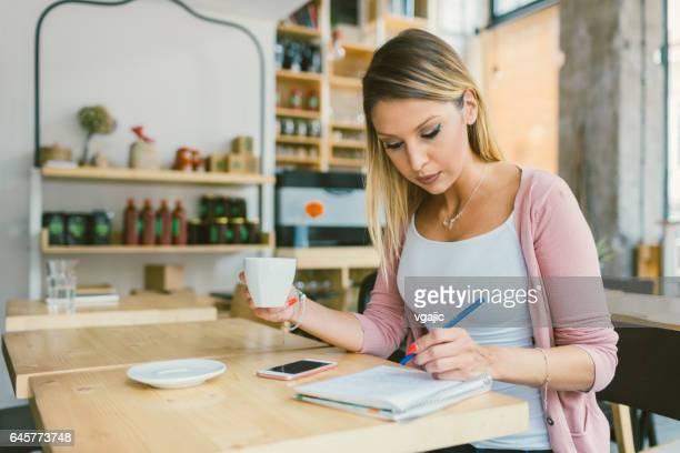 jonge vrouw zitten in het cafe en schrijven - linkshandig stockfoto's en -beelden