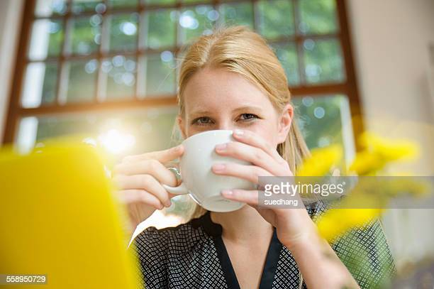 Young woman sitting in cafe, drinking coffee, using laptop