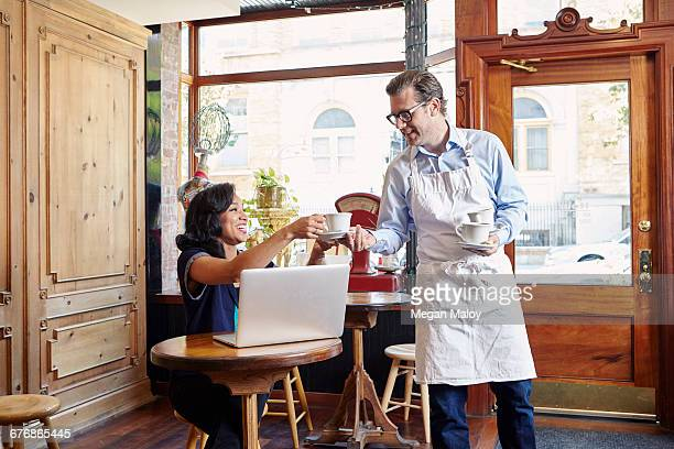 Young woman sitting in cafe, using laptop, male worker taking empty coffee cup