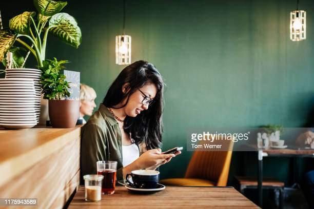 young woman sitting in cafe using smartphone - woman texting stockfoto's en -beelden