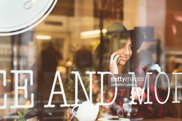 young woman sitting in cafe, using smartphone, view through window - muro stock photos and pictures
