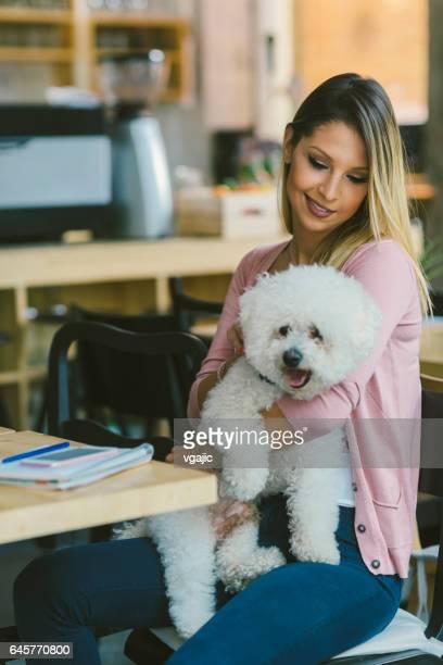 彼女の犬とカフェに座っている若い女性