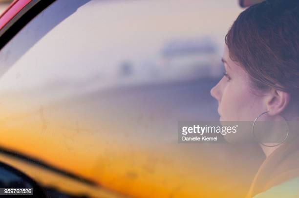 young woman sitting in car behind glass window - sunrise contemplation stock pictures, royalty-free photos & images