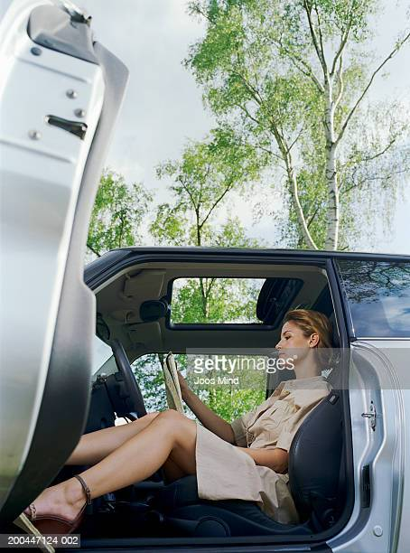 Young woman sitting in car looking at map, view through open car door
