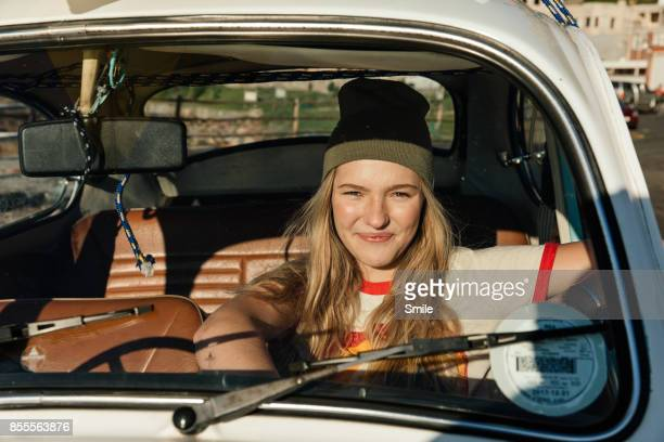 Young woman sitting in car smiling