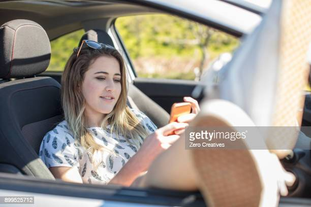 young woman sitting in car, using smartphone, legs out of open car window - legs spread open stock photos and pictures