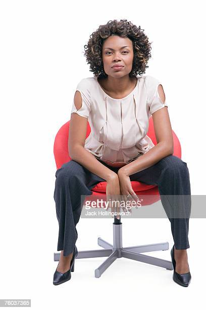 young woman sitting in chair against white background, portrait - legs apart stock pictures, royalty-free photos & images
