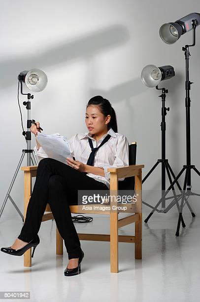 Young woman sitting in chair and studying paper