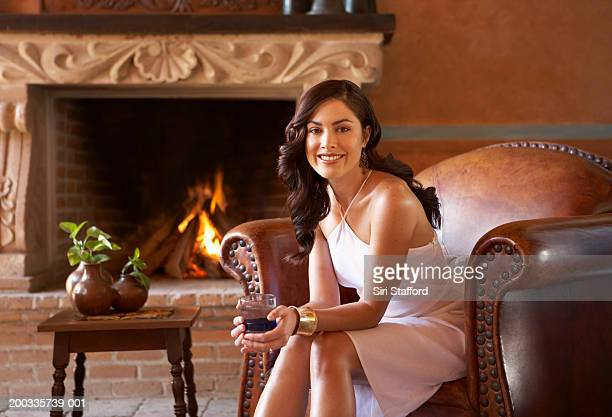 young woman sitting in chair, holding glass, portrait - ホルターネック ストックフォトと画像
