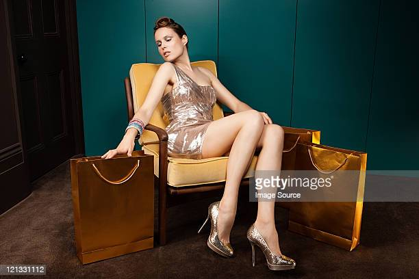 young woman sitting in chair with shopping bags - beautiful legs in high heels stock photos and pictures