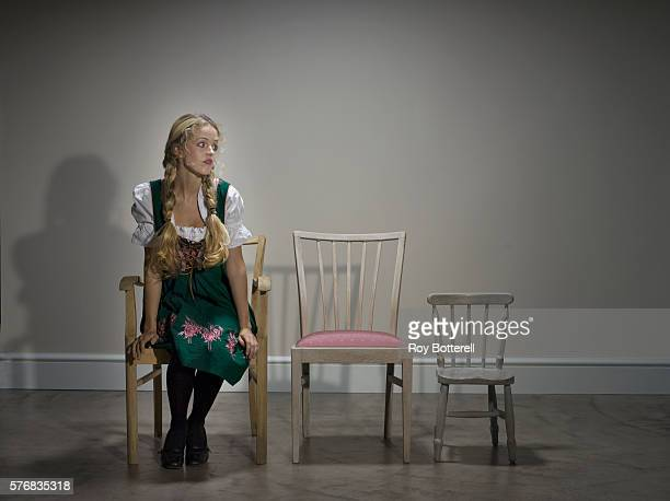 young woman sitting in chairs - goldilocks stock photos and pictures