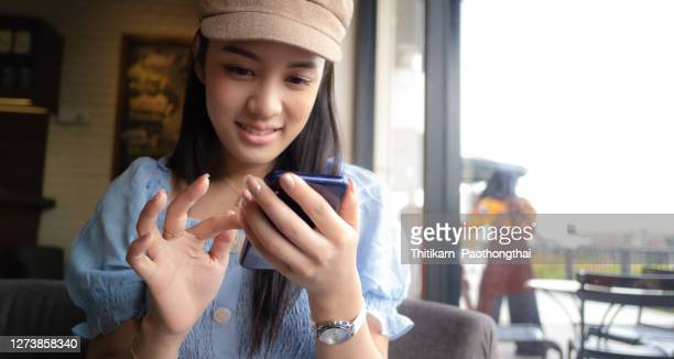 young woman sitting in coffee shop - thai ethnicity stock pictures, royalty-free photos & images