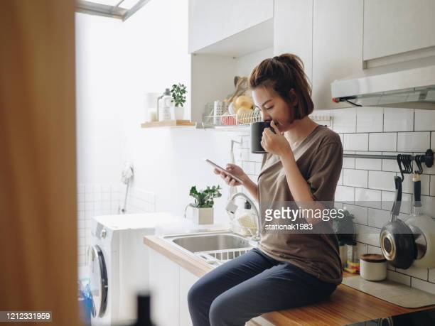 young woman sitting in cozy kitchen and working on her mobile. - coffee drink stock pictures, royalty-free photos & images