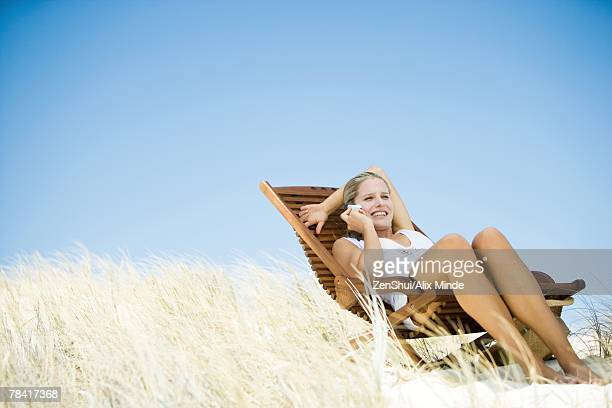 Young woman sitting in deck chair, in dunes, using cell phone