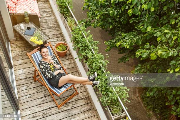 young woman sitting in deck chair, relaxing on her balcony - balcony stock pictures, royalty-free photos & images