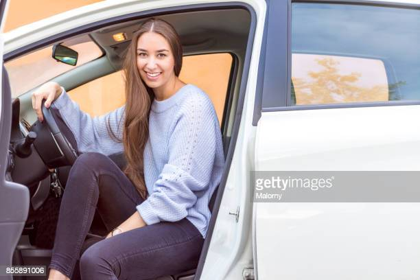 Young woman sitting in drivers seat of a white car.