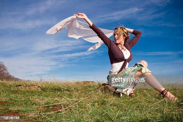young woman sitting in field and holding scarf to wind - wind blowing up skirts stock photos and pictures