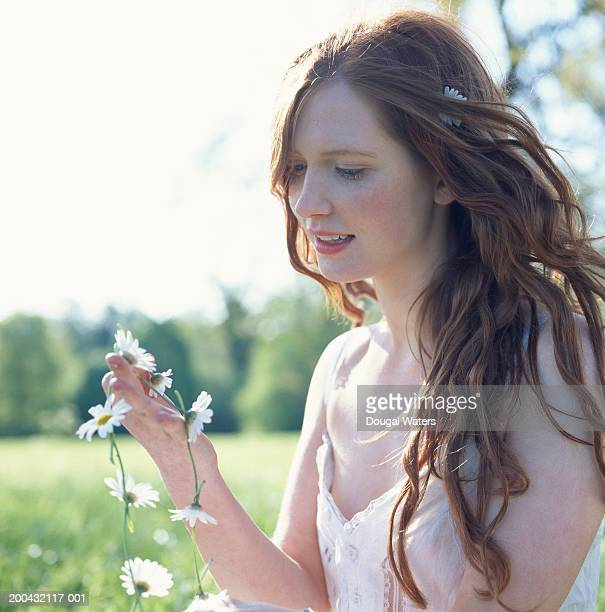 Young woman sitting in field holding daisy chain, smiling