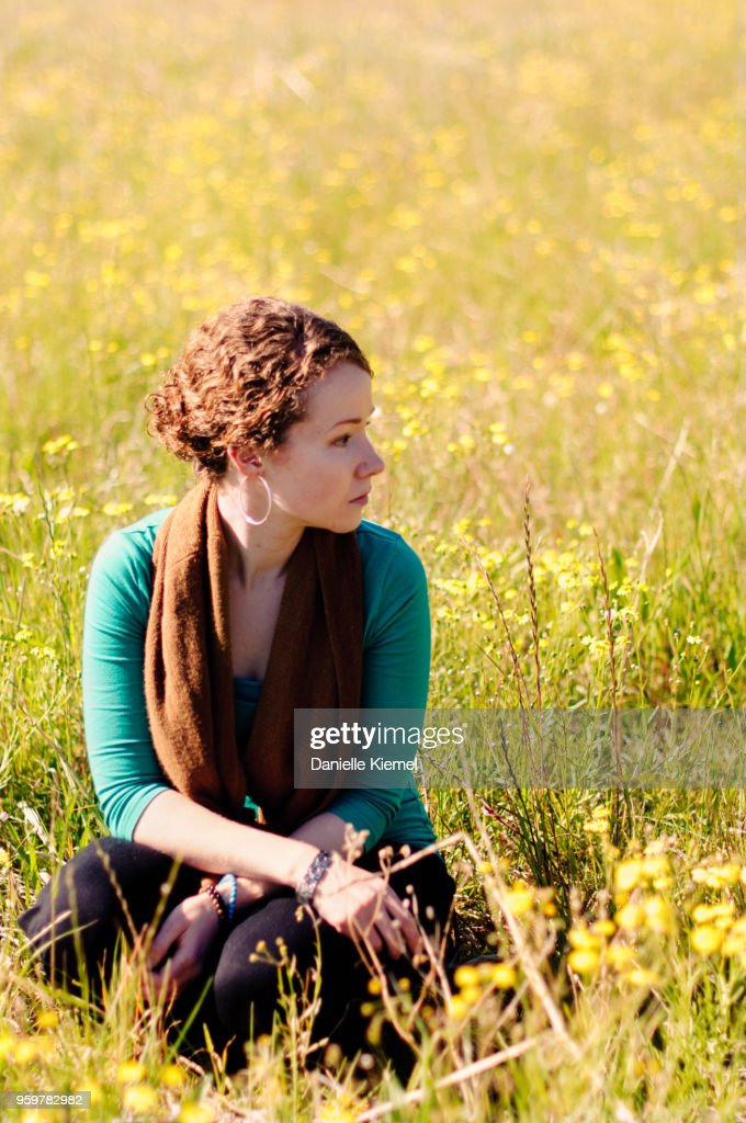 Young woman sitting in field of flowers : Stock-Foto
