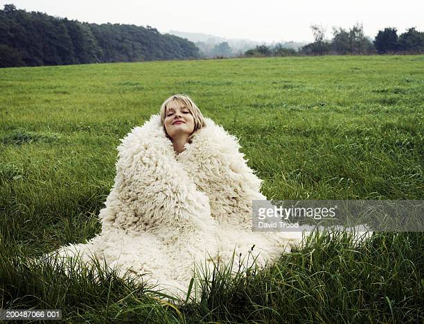 young woman sitting in field wrapped in wool blanket, eyes closed - avvolto in una coperta foto e immagini stock