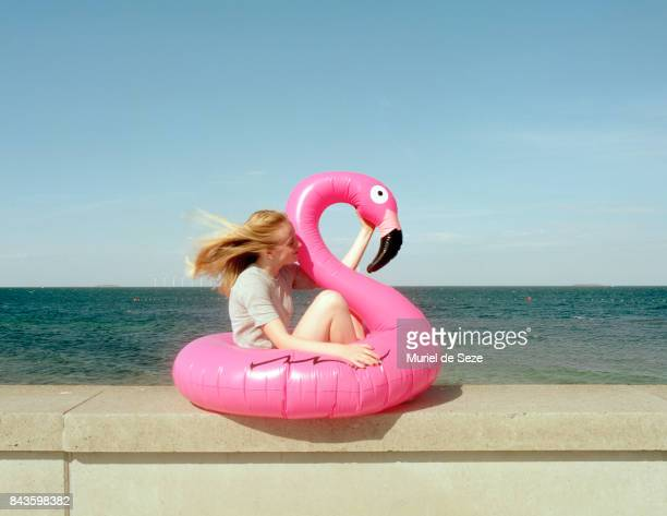 Young woman sitting in flamingo ring.