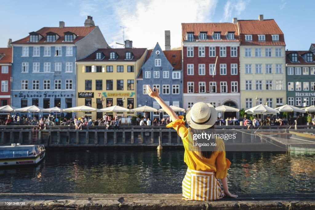 Young woman sitting in front of colorful buildings along Nyhavn (New Harbour), Copenhagen, Denmark : Stock Photo