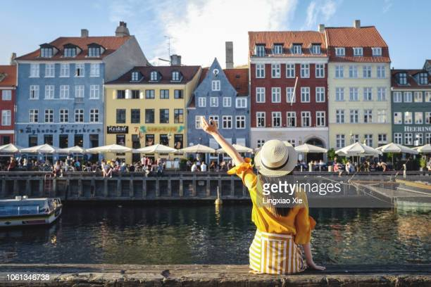 young woman sitting in front of colorful buildings along nyhavn (new harbour), copenhagen, denmark - copenhague photos et images de collection