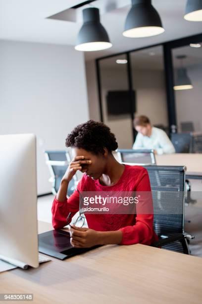 Jonge vrouw achter computer zit en zorgen te maken
