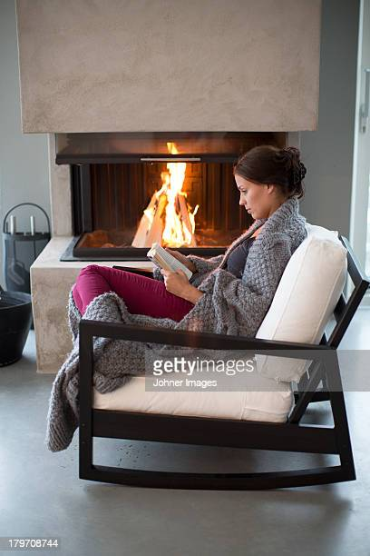 Young woman sitting in front of fireplace and reading