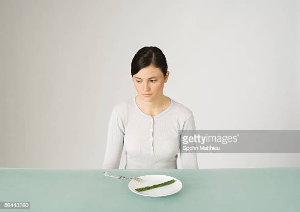 young woman sitting in front of plate with single asparagus, looking away - hongerig stockfoto's en -beelden