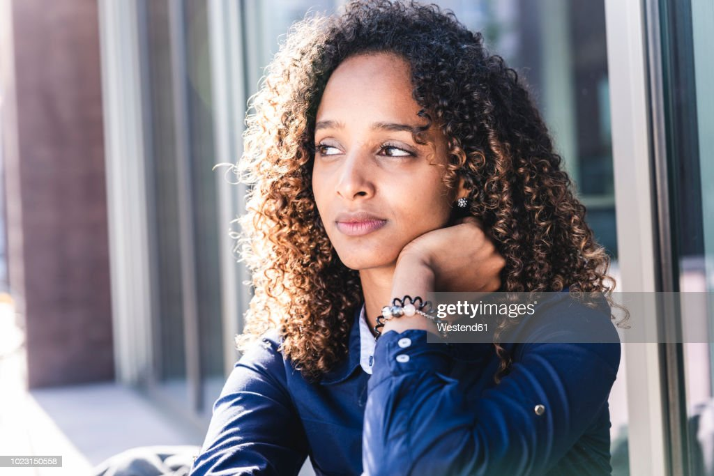 Young woman sitting in front of window in the city, portrait : Foto de stock
