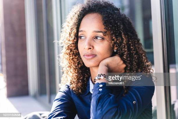 young woman sitting in front of window in the city, portrait - schwarzes haar stock-fotos und bilder