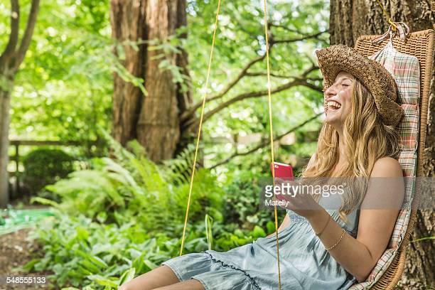 Young woman sitting in garden swing seat laughing