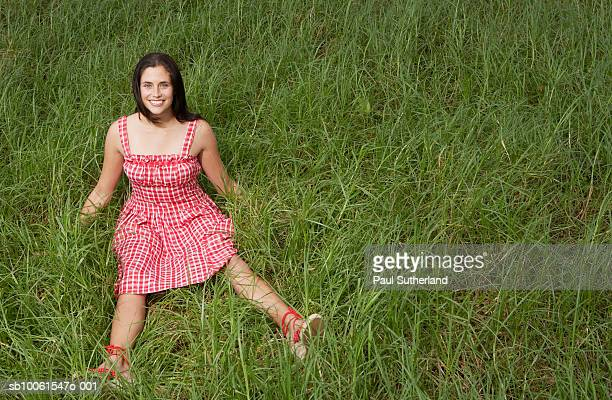 Young woman sitting in grass field, smiling, portrait