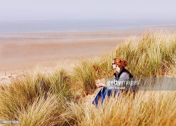 young woman sitting in grass overlooking the sea - norfolk england stock pictures, royalty-free photos & images